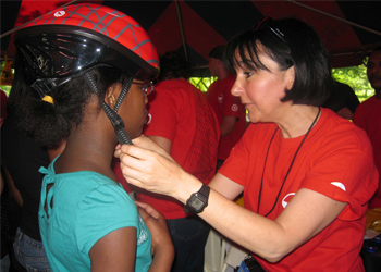 DOT staff teaching young cyclists how to properly fit a helmet