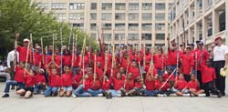 Kids from the New York Emperors Stickball League, honoring fallen Firefighter Steve Mercado (Engine 40), pose with members from the NYPD and the FDNY stickball teams.