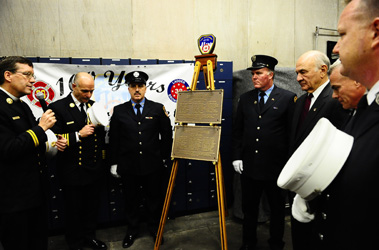 Reverend Stephen Harding blesses the centennial plaques for Engine 88 and Ladder 38 as Fire Commissioner Nicholas Scoppetta, Chief of Department Salvatore Cassano, Capt. Richard Kirschner of Engine 88, Capt. Michael May of Ladder 38 and ceremonial officers stand by.