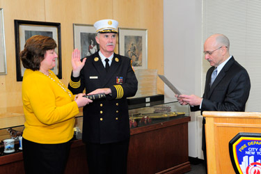 Fire Commissioner Salvatore Cassano administers the Oath of Office to Edward Kilduff, who was sworn in as the FDNY's 34th Chief of Department with his wife, Kathy, at his side.