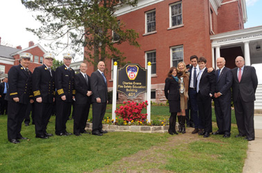 FDNY members and the family of Charles Evans in front of the Charles Evans Fire Safety Education Building. (L to R) FDNY Chaplain Rabbi Joseph Potasnik, Chief of Training Thomas Galvin, Chief of Department Edward Kilduff, First Deputy Commissioner Don Shacknai, Fire Commissioner Salvatore Cassano, Evans' sister and member of the Charles Evans Foundation Alice Shure, Mr. Evans' wife Bonnie Evans, Tony Shure, Charles Evans, Jr., FDNY Foundation Board Member Nicholas Scoppetta and Chairman of the FDNY Foundation Board Steve Ruzow.