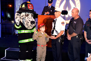 Deputy Chief Anthony Devita and Hot Dog, the FDNY's Fire Safety Mascot, and the members of Ladder 16 stand by Jao Daniel de Barros, as FF Carlos Azevedo, Engine 316, swears him in as a Junior FDNY Firefighter.