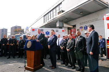 Mayor Bill de Blasio and Fire Commissioner Daniel Nigro address the crowd surrounded by numerous dignitaries and FDNY members