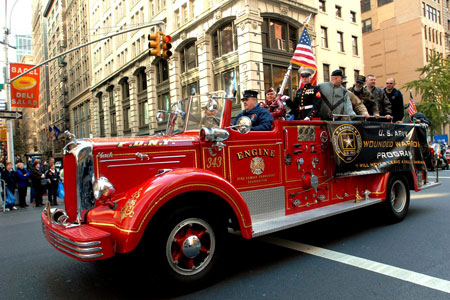 Firefighter Danny Prince drives a ceremonial fire rig carrying veterans who have served in the wars in Iraq and Afghanistan, as well as in World War II and the Korean War. The FDNY supports local veterans through partnerships with the Brooklyn Purple Hearts and Wounded Warriors at Fort Hamilton.