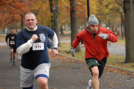 Runners head towards the finish line in the 29th Annual Turkey Trot 5K Run as family and friends cheer them on.