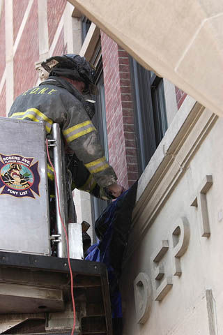 Firefighter Matthew Roberts from Engine 249 and Firefighter Frank Valerio from Ladder 113 hang bunting on the facade of their firehouse in memory of Lt. John Martinson on January 4.