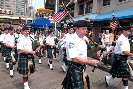 The Emerald Society Pipes and Drums Band leads the crowd to the water at the South Street Seaport to watch the blessing.