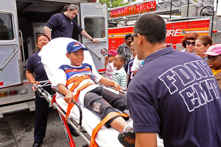 FDNY EMTs show students how they transport a patient in an ambulance.