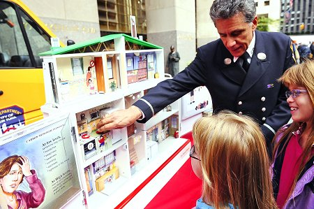 Director of the FDNY Fire Safety Education Unit Lt. Anthony Mancuso shows children how to keep their homes fire safe using the unit's interactive Hazard House.