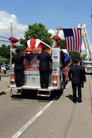Firefighters from Engine 221 and Ladder 104 escort the casket during the funeral procession.