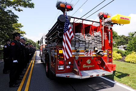 Engine 221's apparatus drives past a lineup of thousands of firefighters in the funeral procession for FF Paul Warhola.