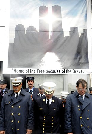 (L to R) Manhattan Borough Commander Chief Michael Weinlein, Chief of Department Salvatore Cassano and First Deputy Commissioner Frank Cruthers join firefighters outside Engine 10/Ladder 10, across the street from the World Trade Center site, during the annual Sept. 11 memorial service.