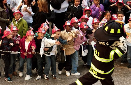 Hotdog gives kids high-fives before they take the Junior Firefighter's Pledge.