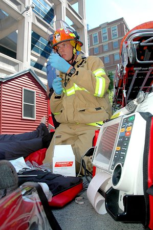 A paramedic treats the victim (a high-tech mannequin) of smoke inhalation and cyanide poisoning.