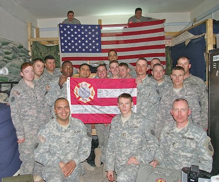 Members of the U.S. Army with the FDNY flag signed by firefighters from Engine 34/Ladder 21 and the American flag that was flown over the firehouse on Sept. 11, 2001.