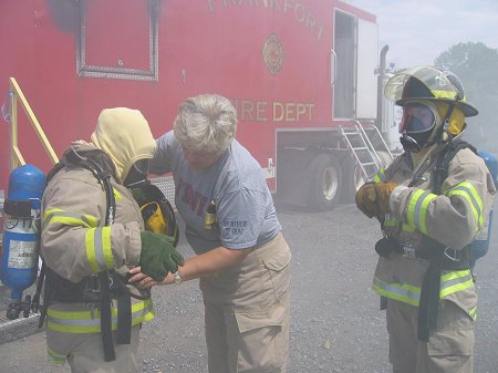 Retired FDNY Firefighter Eileen Gregan helps a camper with her gear.