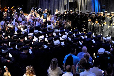 The large crowd at the Intrepid Air, Sea and Space Museum stand as the FDNY Singers sing the National Anthem.