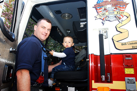 Young boy sits in fire truck during outdoor event.