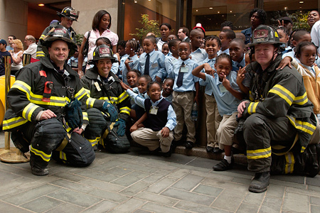Firefighters pose with schoolchildren during outdoor event at Rockefeller Center.